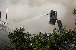 © Licensed to London News Pictures. LONDON, UK  14/06/11. Firefighters hose down flames breaking through the roof of Marconi House on Aldwich in London today (Tuesday). The incident in the building, which was being converted to a luxury hotel and apartments at the time, saw 15 fire engines and 75 firefighters work to control the fire. Please see special instructions for usage rates. Photo credit should read Matt Cetti-Roberts/LNP