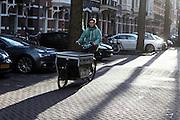 In Amsterdam brengt een bezorger met de bakfiets van Marleen Kookt maaltijden rond. Inwoners van Amsterdam kunnen via de site van marleenkookt.nl maaltijden bestellen.<br /> <br /> In Amsterdam a man delivers food of the cooking service 'Marleen Kookt' (Marleen cooks) with a cargo bike.