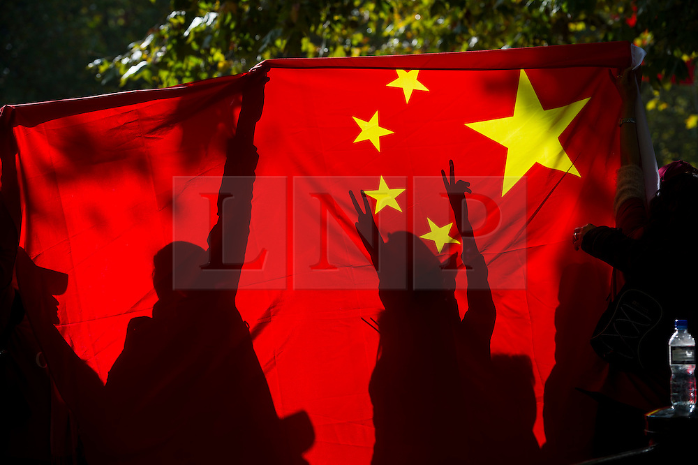 © Licensed to London News Pictures. 20/10/2015. London UK. A group of Chinese people silhouetted against a Chinese flag on The Mall in London as a carriage carrying Queen Elizabeth II and President Xi Jinping makes its way along the Mall to Buckingham Palace as Chinese President Xi Jinping starts day one of a four day State Visit to the United Kingdom. Photo credit: Ben Cawthra/LNP