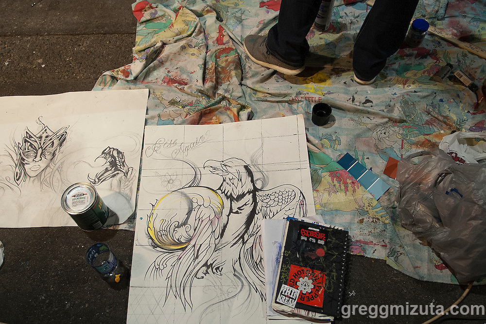 Joseph Durbin sketches lay on the ground as he works on his mural late in the evening of August 6, 2016 during the Freak Alley Gallery sixth annual mural event in downtown Boise, Idaho.<br /> <br /> Joseph didn't realize that he was going to have such a big piece to do. Painting for him is a great outlet. Although he works hard in a manual labor job, putting in the extra work to do something like this was a positive for him.<br /> <br /> He thinks that colorful makes you happy and he has always enjoyed seeing swirls, like Starry Night, and loves the feeling that it gives. He incorporated these into his mural as his way to express a positive message in his work. <br /> <br /> Freak Alley Gallery's week long event provided an &quot;art-in-motion&quot; experience as it welcomed the public to watch artists work on their murals.