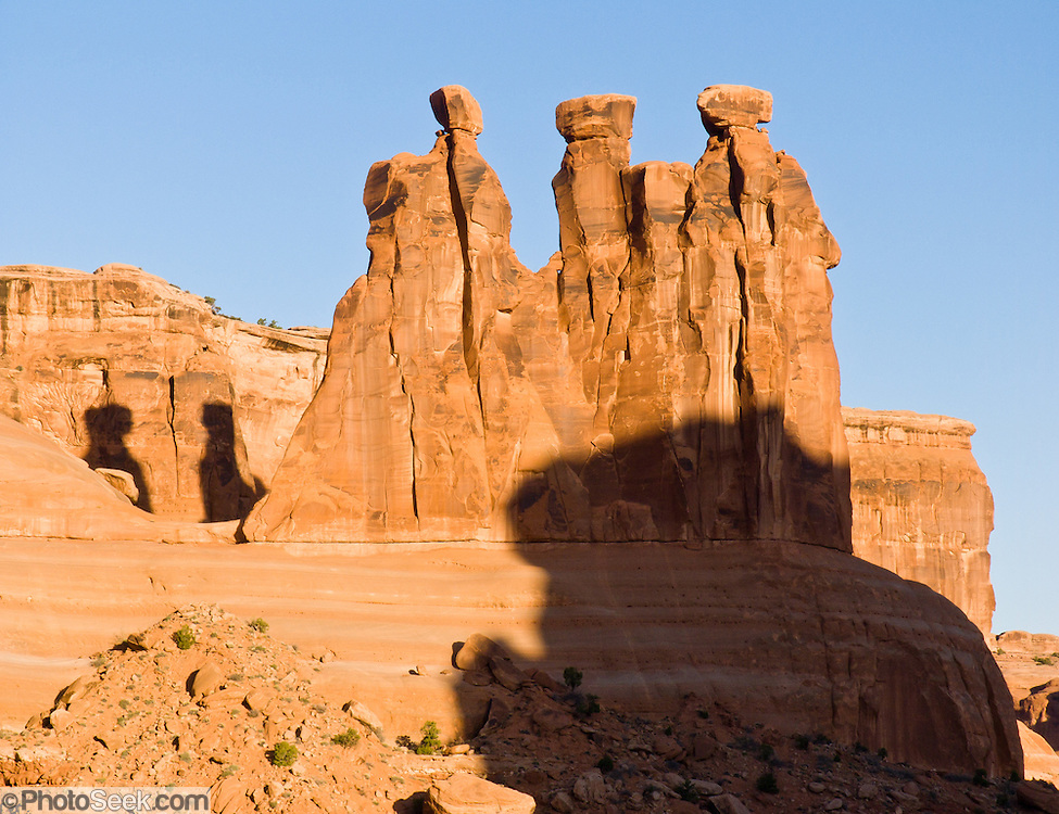 The Three Gossips erode from the Slick Rock member of Entrada Sandstone in Arches National Park, Utah, USA. These rock monuments are beautiful both at sunrise (seen here) and sunset.