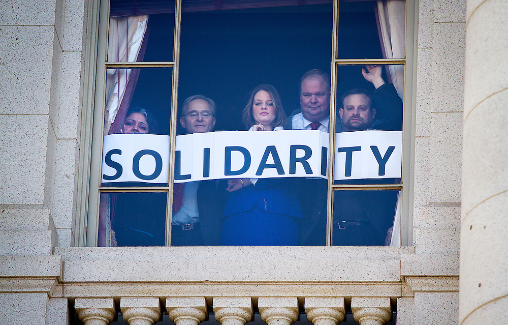 MADISON, WI — FEBRUARY 24: Employees inside the Wisconsin State Capitol show a message of support and solidarity from their window looking over the worker and labor union opposition rally just outside. Workers and labor unions rallied in opposition to a right-to-work bill being discussed in the state legislature.