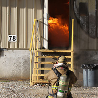 A firefight suits up to start fighting the fire at American Furniture through a service door as they try to contain the fire at their plant in Ecru.