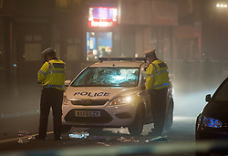 © Licensed to London News Pictures. 29/11/2014.  Bristol, UK. A Police patrol car is examined by police after a collision with a woman in Stokes Croft which was closed to traffic on a busy Saturday night.  The woman suffered potentially life threatening head injuries after the patrol car was on an emergency response call to reports of a man with a knife making threats.  A man was arrested.  Photo credit : Simon Chapman/LNP