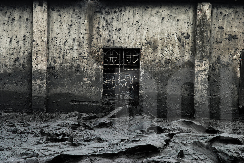 Sea of charcoal in front of a splattered wall with an iron-barred window, Hanoi, Vietnam, Southeast Asia
