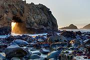 Sunset light shines through a sea cave on Pfieffer Beach, Big Sur, California