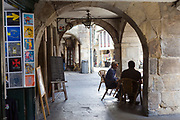 SANTIAGO DE COMPOSTELA, SPAIN - OCTOBER 14th 2017 - Tourists sit and enjoy tapas at a table and chairs within the old architecture and main city of Santiago de Compostela, Galicia, Spain.