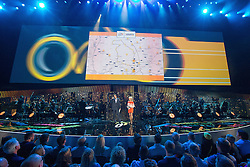 © Licensed to London News Pictures . 03/07/2014 . Leeds , UK . Presenters Jill Douglas and Sebastien Piquet describe the route through Yorkshire . Tour de France Team Presentation in front of a live audience of 10,000 people at the Leeds Arena and worldwide TV audience in excess of 300 million . Photo credit : Joel Goodman/LNP