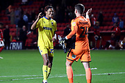 AFC Wimbledon defender Toby Sibbick (20) celebrating with AFC Wimbledon goalkeeper Joe McDonnell (24) during the EFL Trophy match between Charlton Athletic and AFC Wimbledon at The Valley, London, England on 4 September 2018.