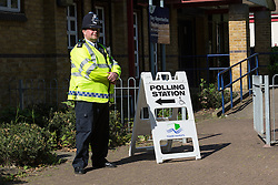 © Licensed to London News Pictures. 11/06/2015. London, UK. A police officer outside a polling station in Stepney, Tower Hamlets, east London. Tower Hamlets residents go to the polls today to vote for a new Mayor of Tower Hamlets after Lutfur Rahman was removed from office for fraud in corrupt practices by an election court earlier this year. Photo credit : Vickie Flores/LNP