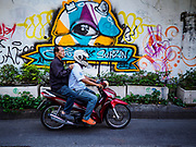 17 DECEMBER 2018 - BANGKOK, THAILAND: A motorcyclist rides past a mural on a wall in a working class neighborhood behind Siam Paragon, an exclusive mall in central Bangkok. According to Credit Suisse Global Wealth Databook 2018, which surveyed 40 countries, Thailand has the highest rate of income inequality in the world. In 2016, Thailand was third, behind Russia and India. In 2016, the 1% richest Thais (about 500,000 people) owned 58.0% of the Thailand's wealth. In 2018, they controlled 66.9%. In Russia, those numbers went from 78% in 2016, down to 57.1% in 2018. The Thai government disagreed with the report and said the report didn't take government anti-poverty programs into account and that Thailand was held to an unfair standard because most of the other countries in the report are developed countries in the Organisation for Economic Co-operation and Development.    PHOTO BY JACK KURTZ