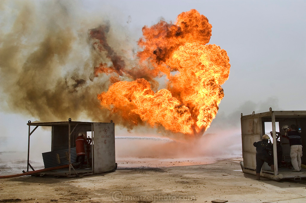 """Firefighters from the KWWK (Kuwait Wild Well Killers) attempt to kill an oil fire in the Rumaila field by dosing the fire with water while guiding a """"stinger"""" that will pump drilling mud into the damaged well. A """"stinger"""" is a tapered pipe on the end of a long steel boom controlled by a bulldozer. Drilling mud, under high pressure, is pumped through the stinger into the well, stopping the flow of oil and gas. The Rumaila field is one of Iraq's biggest oil fields with five billion barrels in reserve. Many of the wells are 10,000 feet deep and produce huge volumes of oil and gas under tremendous pressure, which makes capping them very difficult and dangerous. Rumaila is also spelled Rumeilah.."""