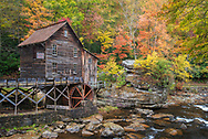 The historic grist mill at Babcock State Park in West Virginia, sits along Glade Creek surrounded by colorful autumn foliage.