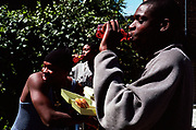Three teenage boys drinking red soft drink and eating take-away burgers Lambeth Walk South London c.2000