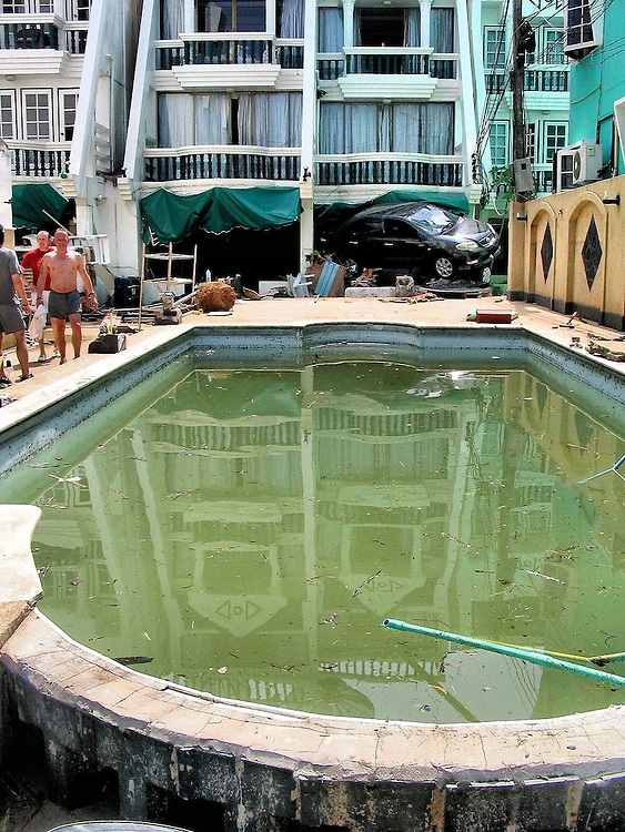 Car Wedged into Hotel After Tsunami on Patong Beach in Phuket, Thailand <br /> Surprisingly, there is not much debris in this swimming pool.  Behind it, however, there is a car wedged into the hotel&rsquo;s window in Phuket, Thailand.  The balconies above look unharmed but the tsunami waves typically blew through the lower three floors of the hotels along Patong Beach.
