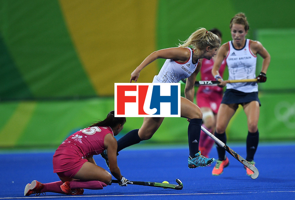 Japan's Yukari Mano (L) tries to hit past Britain's Sophie Bray (C) during the women's field hockey Japan vs Britain match of the Rio 2016 Olympics Games at the Olympic Hockey Centre in Rio de Janeiro on August, 11 2016. / AFP / MANAN VATSYAYANA        (Photo credit should read MANAN VATSYAYANA/AFP/Getty Images)