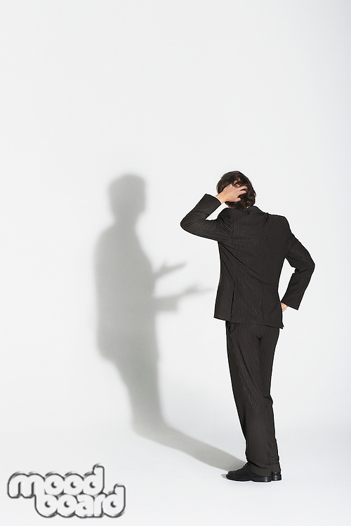 Young businessman standing hand on head and hip arguing with own shadow