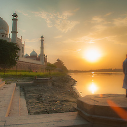 Boy making a phone call in front of the backside of the Taj Mahal at sunset, Agra, India.