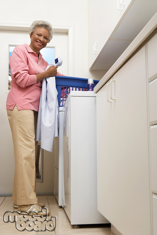 Senior woman doing laundry at home