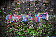 Multi-colored doormats dry on a wall ledge in Hue, Vietnam, Southeast Asia
