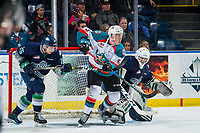 KELOWNA, CANADA - JANUARY 30:  Cayde Augustine #5 of the Kelowna Rockets is stick checked by Owen Williams #25 at the net of Roddy Ross #1 of the Seattle Thunderbirds on January 30, 2019 at Prospera Place in Kelowna, British Columbia, Canada.  (Photo by Marissa Baecker/Shoot the Breeze)