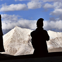 A pilgrim pray watch the view during the Hemis Festival in honor of Guru Padma Sambhav´s birth anniversary, at the Hemis Monastery, 40 km from Leh, India,  It also has the largest Thangkha in  Ladakh, which is unfurled, once in 12 years. July 2004.