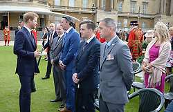 Prince Harry speaks to guests during the Not Forgotten Association Annual Garden Party at Buckingham Palace, London.