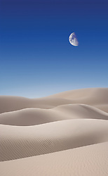 Desert sand dunes against a blue sky with a mid-day moon