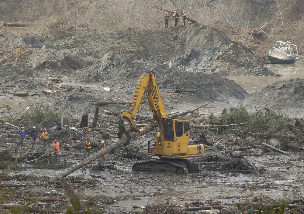 An excavator moves a tree trunk as search work continues in the mud and debris from a massive mudslide that struck Oso near Darrington, Washington March 30, 2014. The official death toll from the March 22 catastrophe northeast of Seattle stood at 18, based on the number of victims whose bodies have been recovered and positively identified by medical examiners. But Snohomish County authorities have acknowledged finding 10 more sets of remains that have yet to be identified, putting the overall presumed body count at 28.  REUTERS/Jason Redmond (UNITED STATES)