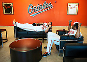 Orioles first baseman Chris Davis (19) and outfielder Chris Dickerson (60) lounge in the lobby of the Orioles baseball complex for their turn with the team's video crew during photo day. Each spring training the players spend a morning in full uniform being photographed by various media outlets and the team's photographers.