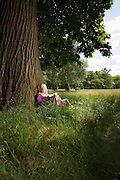 Woman Sitting Beneath a Tree Reading a Book