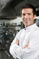 Male chef with arms crossed in kitchen portrait