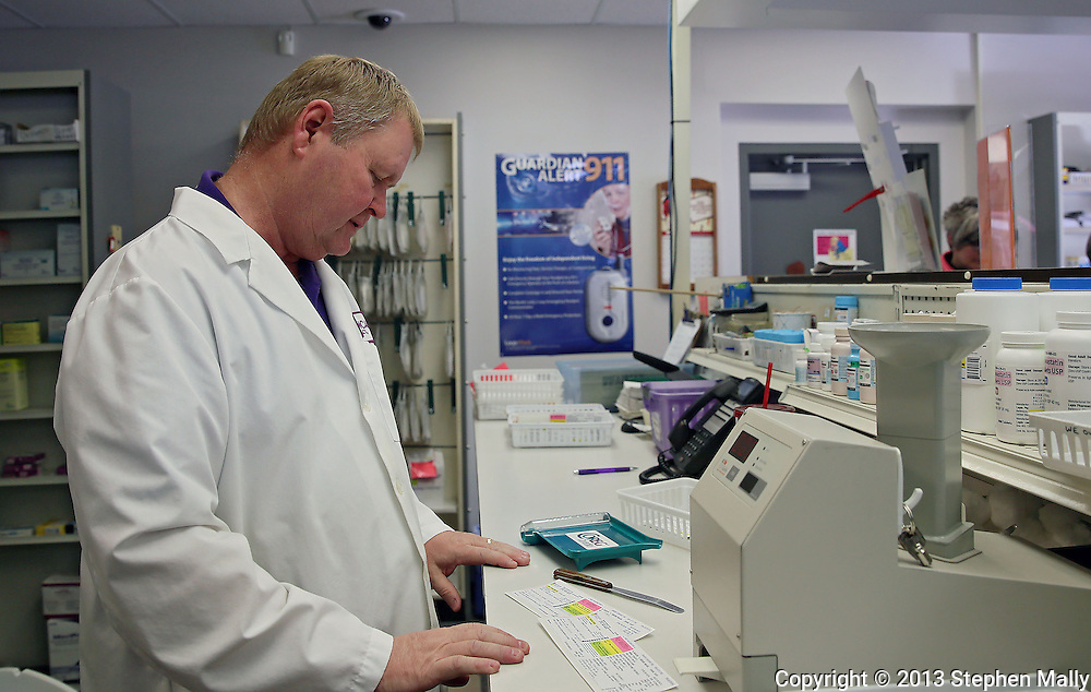 Pharmacist Gary Grabe looks over paperwork for a prescription at Medicap Pharmacy in Cedar Rapids on Tuesday, March 19, 2013.