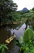 Children paddling a bamboo raft in the river that passes in Santo Antonio do Principe, the capital village of the island.