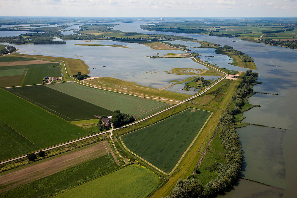 Nederland, Brabant, Gemeente Werkendam, 12-06-2009; polder Noordwaard in de Biesbosch, onderdeel van 'Ruimte voor de Rivier' (bescherming tegen hoogwater door rivierverruiming). Door het gedeeltelijke afgraven van de dijken zijn in- en uitstroomopeningen in de Merwededijk gemaakt (boven in beeld) en is een doorstroomgebied ontstaan waardoor de kans op overstromingen (in de bovenloop) kleiner is. Het deel van de polder wat nu nog landbouwgrond is, onder in beeld, zal in de toekomst ook ontpoldert worden..Polder Noordwaard (part of Biesbosch National Park), part of the program 'Space for the River' (protection against high water by means of creating space for rivers)..Because the dike next to the river has been partly excavated, entrances for the water of the river have been made (left, above middle). The former polder left of the dike can now store water and allows the river to flood more easily downstream (direction of the Northsea). These mesures dimishes the risk of floods further upstream at high water in the winter. The remaining polder (below) will be 'depoldered' in the future. ).Swart collectie, luchtfoto (25 procent toeslag); Swart Collection, aerial photo (additional fee required).foto Siebe Swart / photo Siebe Swart