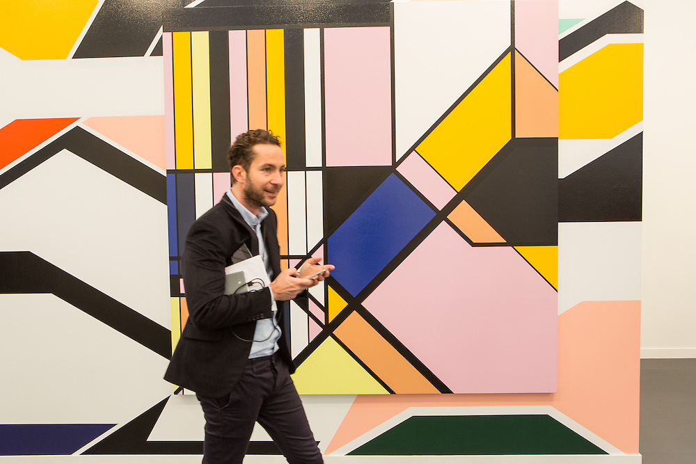 New York, NY - 6 May 2016. Frieze New York art fair. A man walks in front of two paintings by Sarah Morris, one paint on canvas, mounted over a larger painting made directly on a wall, in the White Cube Gallery.