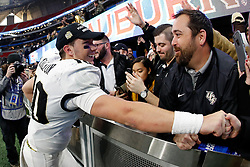 UCF Knights quarterback McKenzie Milton (10) celebrates beating the Auburn Tigers during the 2018 Chick-fil-A Peach Bowl NCAA football game on Monday, January 1, 2018 in Atlanta. The UCF Knights won 34-27. (Paul Abell / Abell Images for the Chick-fil-A Peach Bowl)