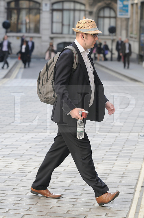 © Licensed to London News Pictures. 24/04/2013.City worker with a sun hat on at Fenchurch Avenue, London..A sunny commute this morning (24.04.2013) for commuters arriving for work in London.  .Photo credit : Grant Falvey/LNP