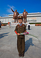Kid in army uniform paying respect to the two statues of the Dear Leaders in Grand Monument Of Mansu Hill in Pyongyang, North Korea.
