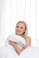 Portrait of attractive young woman covering herself with bedsheet in bed