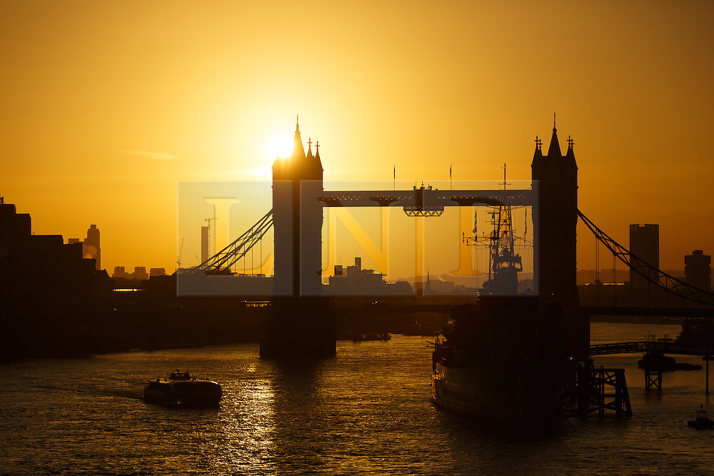 © Licensed to London News Pictures. 10/10/2014. London, UK. An orange sunrise over Tower Bridge on the River Thames in London is seen with clear sky and fine weather this morning. Photo credit : Vickie Flores/LNP