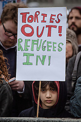 © Licensed to London News Pictures. 19/03/2016. London, UK. A young boy stands with a placard in support of refugees. Thousands march through central London on UN anti-racism day to demand that the British government accept a greater share of refugees seeking asylum in Europe. Photo credit : Rob Pinney/LNP