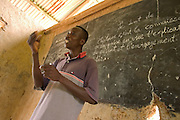 Togolese man teaching in a classroom in a small village along the Togolese border, Eastern Ghana. Thousands of Togolese citizens crossed the border into Ghana after the violence that followed presidential elections in April 2005. Partly because of strong cultural ties between populations on both sides of the border, Togolese refugees were able to enjoy the relative hospitality of their Ghanaian neighbours, and are today scattered in various villages across the border. The UNHCR complains that, since the refugees aren't concentratred in large camps, media attention has been minimal, and that it has been very difficult to attract funding.