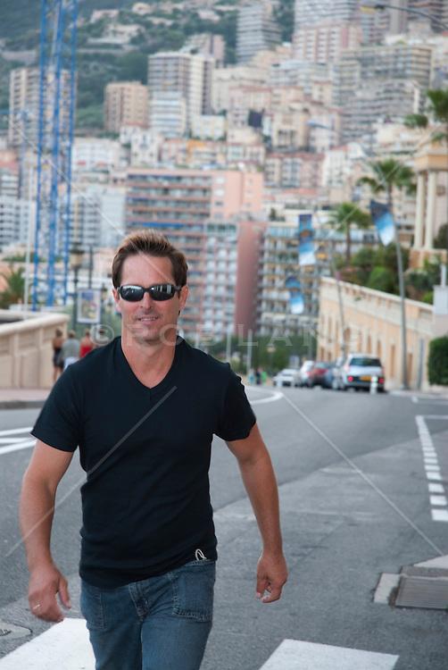 man in sunglasses walking on the street in Monaco