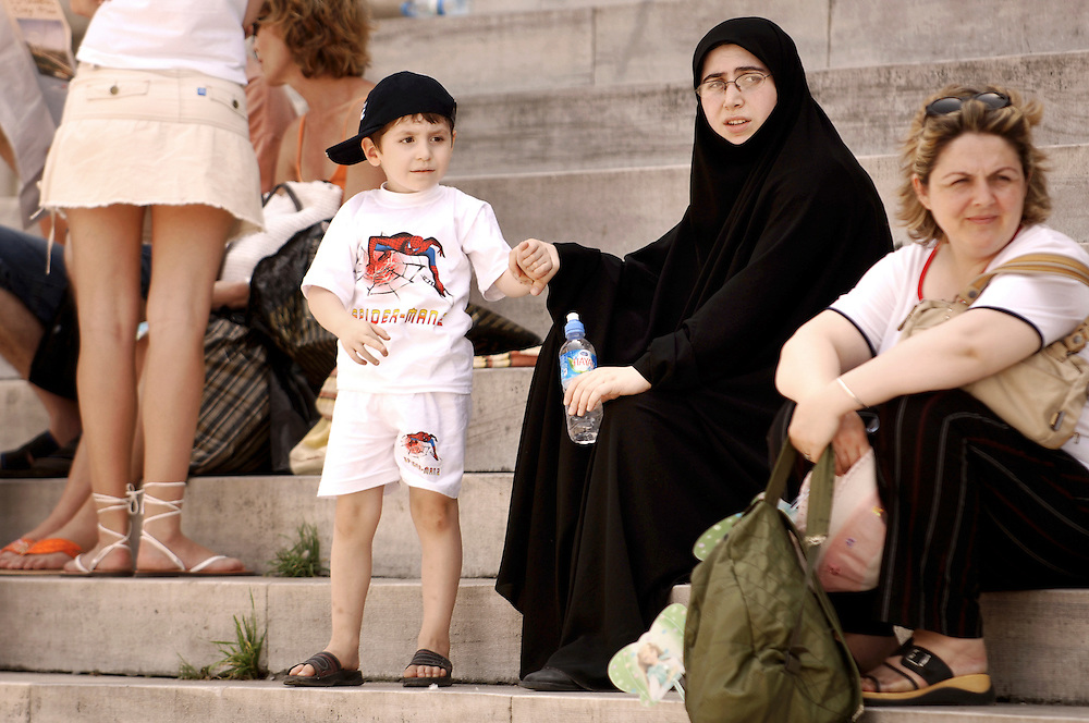 Istanbul , Turkey 06 July 2005<br /> Contrasting cultures represented by two women and child on the steps of a mosque.<br /> Photo: Ezequiel Scagnetti
