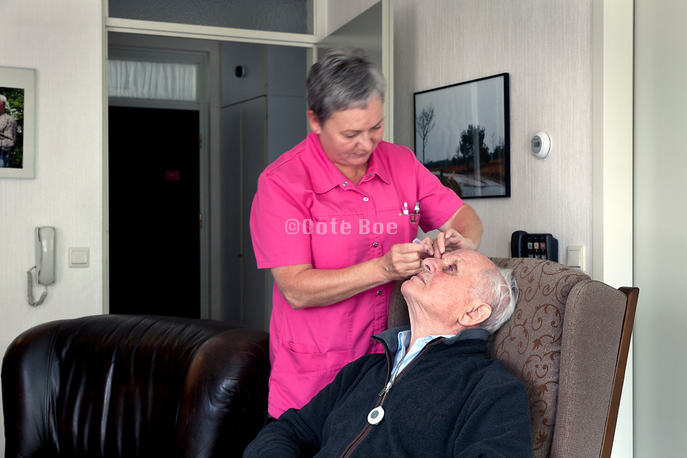 eye dripping of senior 90+ aged man by nurse