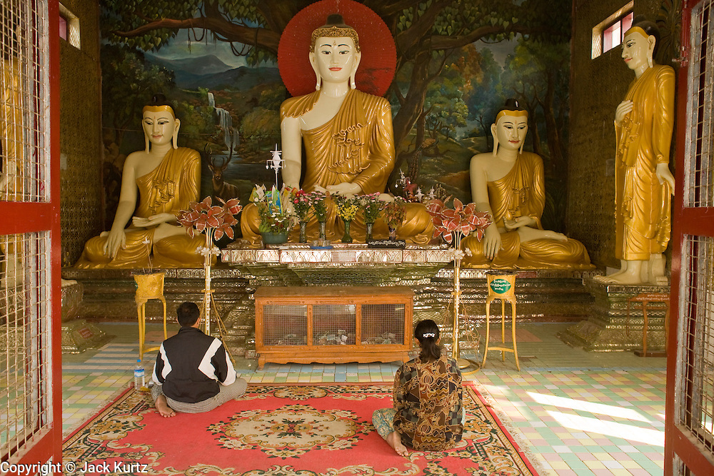 26 FEBRUARY 2008 -- MYAWADDY, MYANMAR: People pray in the Shwe Minn Wany temple in Myawaddy, Myanmar (Burma). Myawaddy, a city of 65,000, is just across the Moei River from Mae Sot, Thailand and is one of Myanmar's leading land ports for goods going to and coming from Thailand. Most of the businesses in the town are geared towards trade, both legal and illegal, with Thailand. Human rights activists from Myanmar maintain that the Burmese government controls the drug smuggling trade between the two countries and that most illegal drugs made in Myanmar are shipped into Thailand from Myawaddy.   Photo by Jack Kurtz