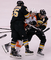 Boston, MA - Boston Bruins defenseman Johnny Boychuk (55) and center Patrice Bergeron sandwich Philadelphia Flyers defenseman Kimmo Timonen in the first period at TD Garden on December 11, 2010.   Photo by Matthew Healey