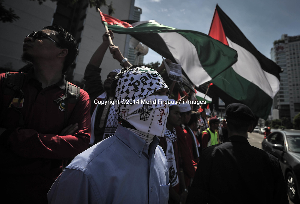Image licensed to i-Images Picture Agency. 18/07/2014. Kuala Lumpur,Malaysia. Demonstrators wears a mask as they protest against Israel's military action in Gaza during a demonstration in front of the US embassy in Kuala Lumpur on July 18, 2014.Picture by Mohd Firdaus / i-Images