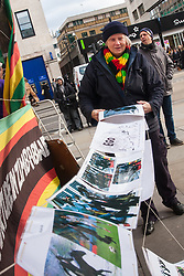 Lodon, February 21st 2015. Dozens of exiled Zimbabweans gather outside their embassy in London proclaiming Mugabe's last birthday in office. Singing and dancing as they have done every Saturday since 2002, the group spoke with passersby and added yet more names to their petition. PICTURED: One of the Zimbabwe Vigil organisers, Rose Benton, who has attended every vigil at the Zimbabwean embassy since 2002, hangs up posters displaying the many meme images of Mugabe's recent fall.